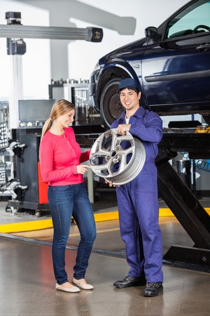 hubcap: Portrait of smiling mechanic holding hubcap with female customer examining it at garage