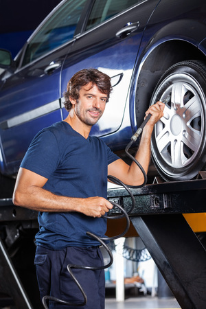 refilling: Portrait of confident male mechanic refilling air into car tire at garage
