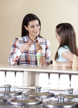 gelati: Happy woman having ice cream with daughter at counter in parlor