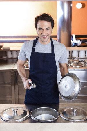 gelati: Portrait of confident waiter holding scoop and lid at ice cream parlor Stock Photo