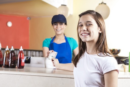parlor: Portrait of happy preteen girl giving dollar note to waitress at counter in ice cream parlor Stock Photo