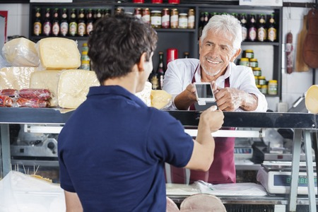 accepting: Smiling salesman accepting payment from male customer in cheese shop