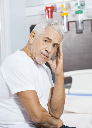 long depression: Portrait of sad male patient sitting on bed at rehab center Stock Photo