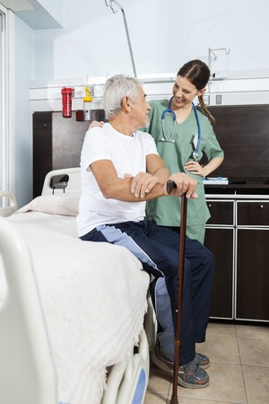 long term care services: Happy senior patient and nurse looking at each other in rehabilitation center Stock Photo