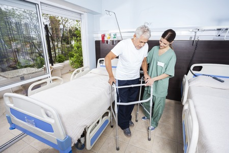 long term care services: Female caretaker helping senior patient with walker in rehab center