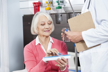 doctor giving glass: Smiling senior patient holding medicine organizer while doctor giving her water glass in rehab center