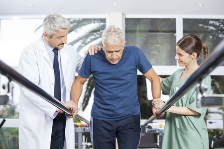 Male and female physiotherapists motivating senior patient to walk between parallel bars in fitness studio Stockfoto