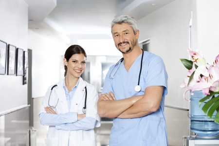 physiotherapists: Portrait of confident male and female physiotherapists standing arms crossed in rehab center