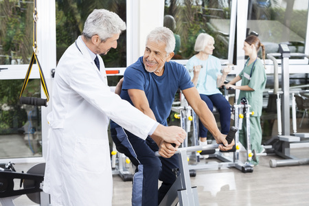 Happy senior man looking at doctor while cycling in fitness studio of rehab center