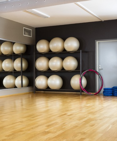 hoops: Hoops leaning on rack of exercise balls in health club Stock Photo