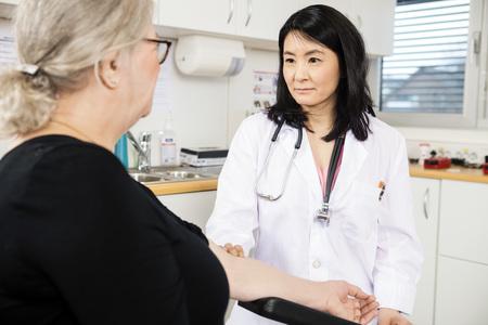 Mitte Erwachsenen zuversichtlich Arzt berühren Arm Senior Patienten vor Bluttest in der Klinik Standard-Bild
