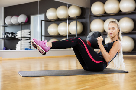 fitness center: Full length portrait of confident woman exercising with medicine ball in gym Stock Photo