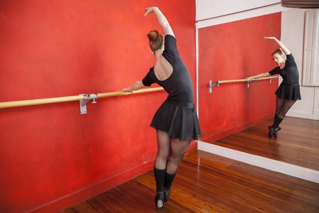 ballet bar: Full length of young ballerina practicing in front of mirror at ballet studio