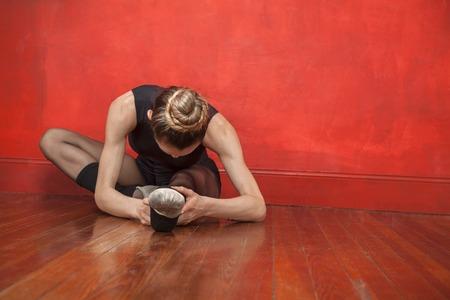 hardwood floor: Young ballerina stretching her legs on hardwood floor in studio