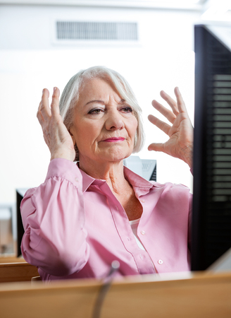 senior women: Stressed senior woman gesturing while looking at computer in classroom
