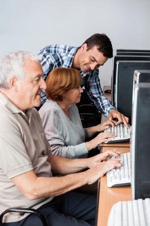 personas ayudando: tutor masculino a la mujer mayor en el uso de la computadora en el aula