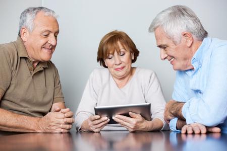 senior men: Happy senior men and woman using digital tablet at table in classroom