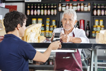 Senior salesman accepting mobile payment from male customer in cheese shop