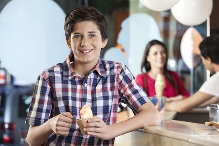 mama e hijo: Retrato de niño sonriente con helado mientras que la madre y el camarero coloca en el contador en el salón