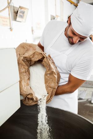 Mi boulanger adulte verser la farine en mélangeant la machine à la boulangerie