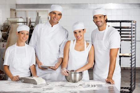 Ritratto di sorridere con tavoletta digitale maschio e femmina di Baker insieme a tavola in forno photo