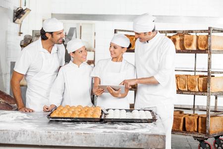 Sorridente tavoletta digitale utilizzando maschio e femmina di Baker a tavola in forno photo