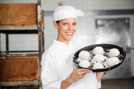 Ritratto di giovane donna che trasportano palline di pasta in teglia da forno a sorridere photo
