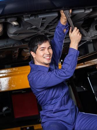 service man: Portrait of confident mechanic repairing underneath car at auto repair shop