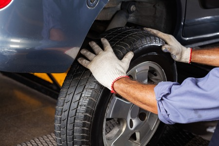 Cropped image of mechanic fixing car tire at garage