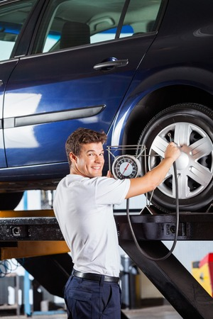 refilling: Portrait of smiling mechanic holding gauge while refilling car tire at garage Stock Photo