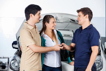 Coppia felice di dare le chiavi per meccanico in piedi davanti alla macchina a negozio di riparazione auto photo
