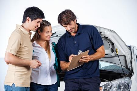meccanico maschio spiegando documenti a coppie in negozio di riparazione auto photo