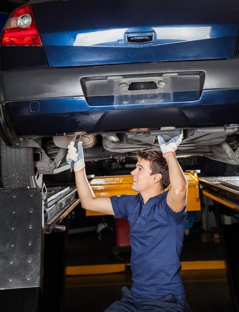 lift: Male mechanic repairing lifted car at auto repair shop Stock Photo