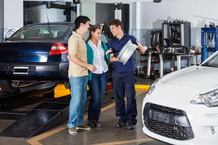 tecnico maschio felice e di coppia che discute sopra coprimozzo metallico in garage photo