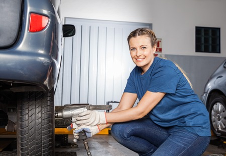 woman portrait: Portrait of smiling female mechanic fixing car tire with pneumatic wrench at auto repair shop Stock Photo