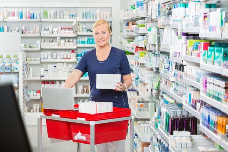 Ritratto di sorridere maturo femminile del farmacista aggiornamento magazzino in computer portatile a farmacia photo
