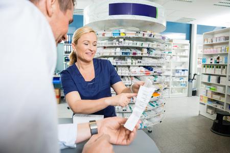Sorridente farmacista spiegando i dettagli del prodotto al cliente in farmacia photo