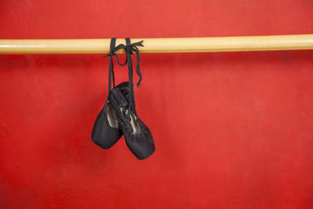 barre: Old ballet shoes hanging from barre against red wall