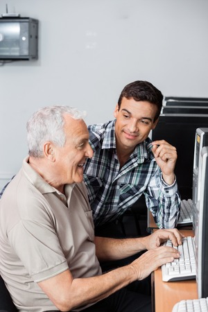 the elderly tutor: Male teacher assisting senior man in using computer at lab