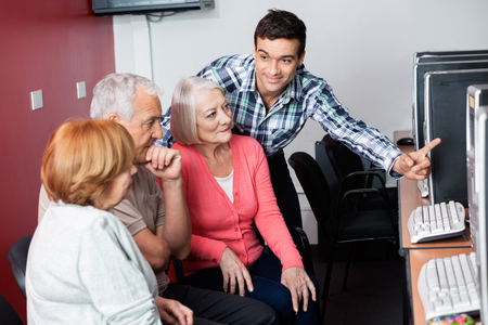 the elderly tutor: Male teacher assisting senior students in using computer at class