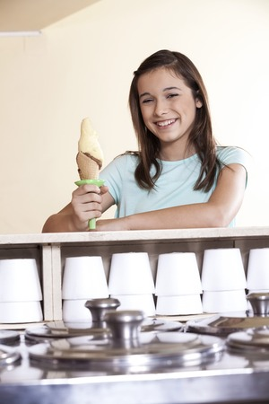 parlor: Portrait of smiling girl holding vanilla ice cream cone at counter in parlor Stock Photo