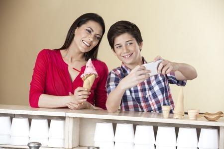 mama e hijo: niño feliz teniendo autorretrato con la madre que sostiene el helado de fresa en el salón de Foto de archivo
