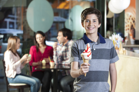 child ice cream: Portrait of smiling boy holding vanilla ice cream cone with family sitting in parlor Stock Photo