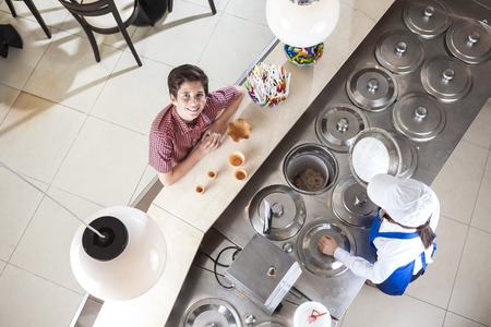gelati: High angle portrait of smiling boy buying ice cream from waitress at counter in parlor Stock Photo