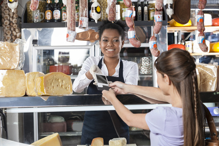 accepting: Young saleswoman accepting payment through credit card from customer at cheese shop