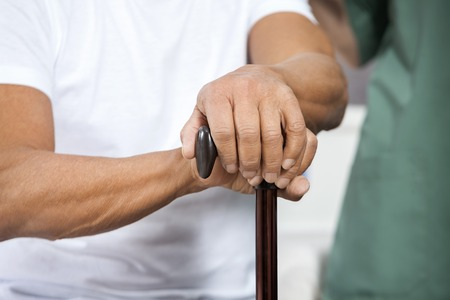 rehab: Midsection of senior man holding cane in rehab center Stock Photo