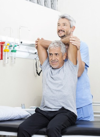 Mature male physiotherapist assisting senior man in exercising at rehab center Stock Photo