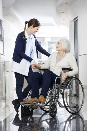 long term care services: Friendly physiotherapist consoling senior patient in wheelchair at rehab center