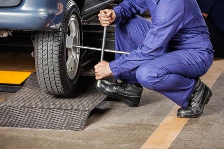 Sezione bassa del meccanico di sesso maschile accovacciata mentre il fissaggio dei pneumatici auto al negozio di riparazione photo