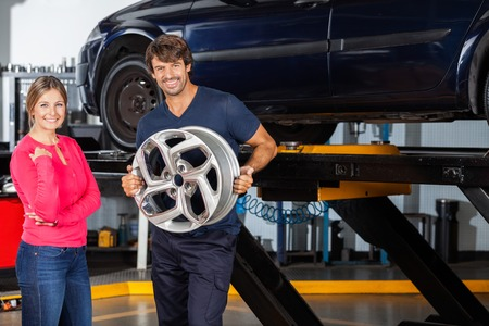 hubcap: Portrait of confident mechanic holding hubcap while standing with female customer at garage
